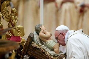 Pope Francis kisses a baby Jesus statue as he leads the midnight Christmas Mass in Saint Peters Basilica at the Vatican late 24 December 2015. ANSA/ALESSANDRO DI MEO